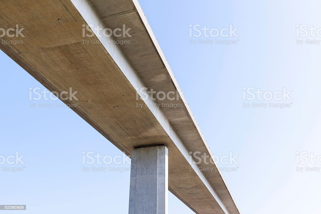 Elevated concrete road bridge from below with plain blue sky stock photo