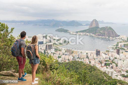 Backpacking tourists standing with views of Sugar Loaf Mountain in Rio de Janeiro, boyfriend and girlfriend backpackers with rucksacks, looking at view