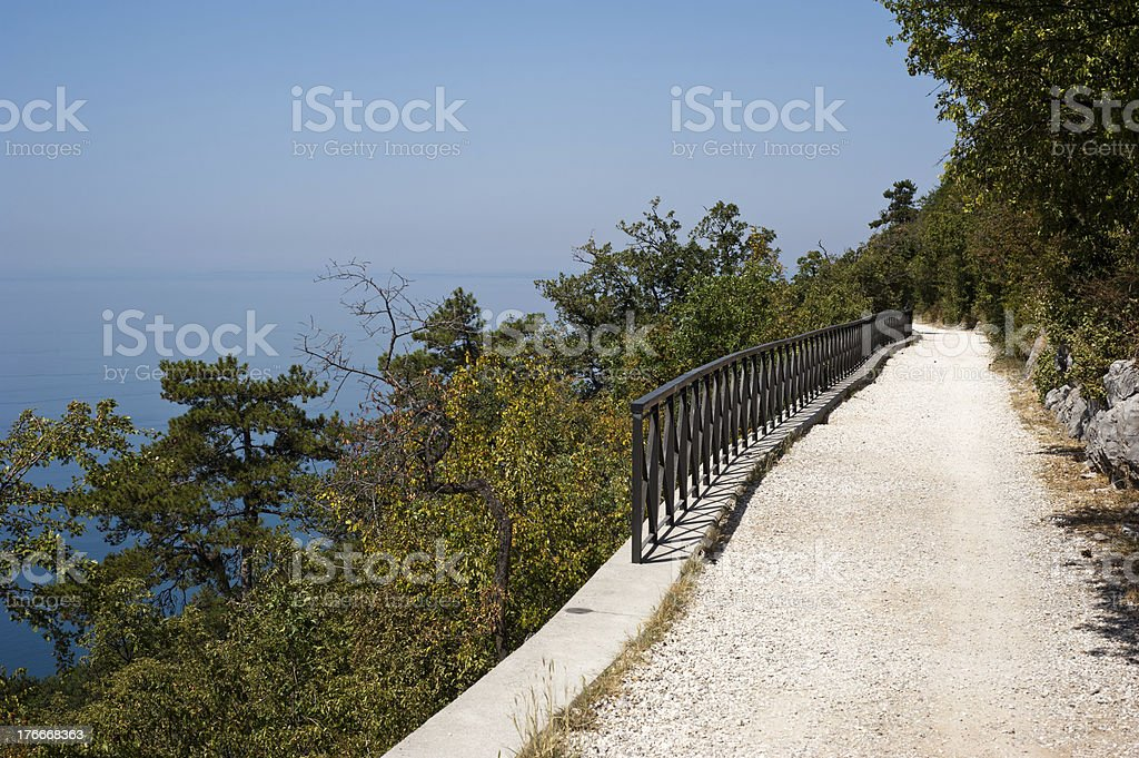 Elevated sun-drenched trail facing the blue sea royalty-free stock photo