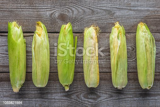 elevated view of autumnal corn cobs on grey wooden tabletop