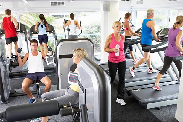 vista elevada de negocios hacen ejercicio en el gimnasio con las máquinas - lleno fotografías e imágenes de stock