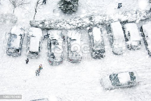 Elevated view of children play in frozen city street with snow covered parking lot during snowing