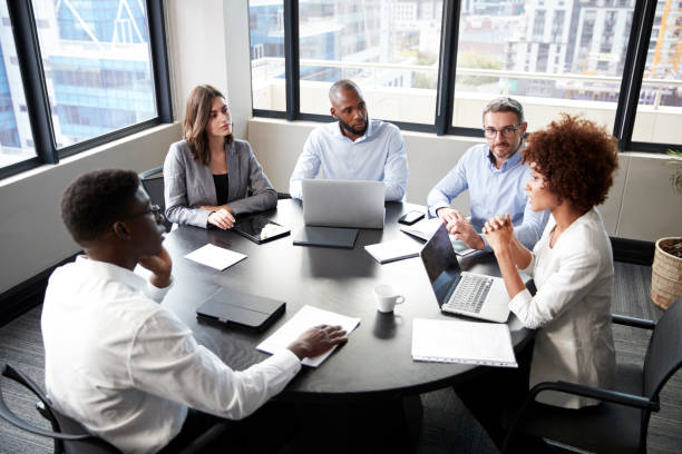 elevated view of corporate business colleagues talking in a meeting room - business meeting, table view from above foto e immagini stock