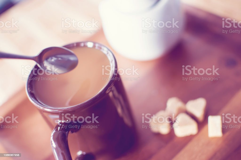 Elevated view of cup of coffee on wood table with spoon and sugar cubes stock photo