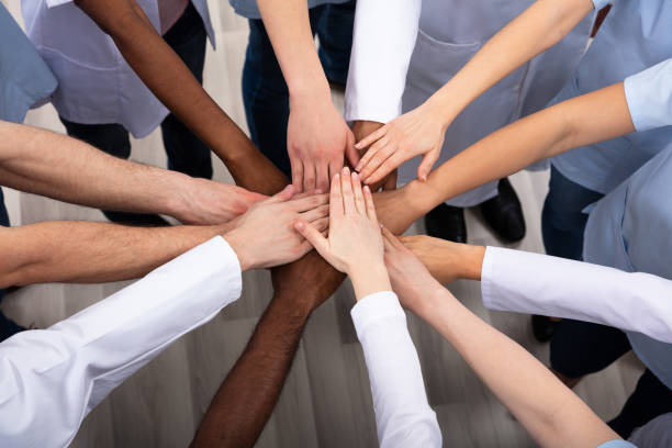 Elevated View Of Doctors Stacking Hands Directly Above Shot Of Medical Team Stacking Hands Together At Hospital community health stock pictures, royalty-free photos & images