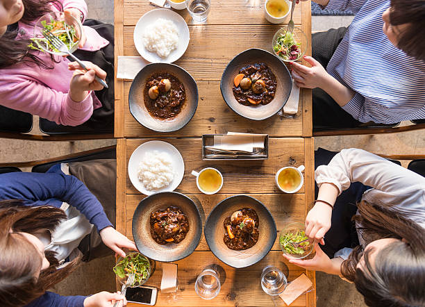 elevated view of four women eating. - japanisches essen stock-fotos und bilder