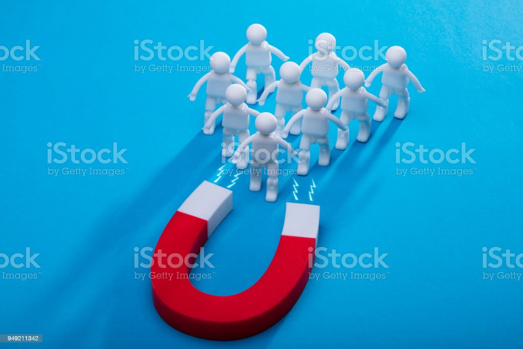 Elevated View Of Horseshoe Magnet Attracting Human Figures stock photo