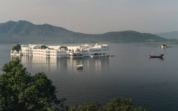 Elevated view of lake Pichola and lake Palace. Udaipur, India. Elevated view of Lake Pichola and Lake Palace hotel with Aravalli hills in background on a bright morning in Udaipur, Rajasthan, India. lake palace stock pictures, royalty-free photos & images
