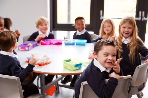 いくつかカメラを顔に回って自分のランチパックを食べる小学校の子供たちのラウンド テーブルに一緒に座っての立面図 - disabilitycollection ストックフォトと画像