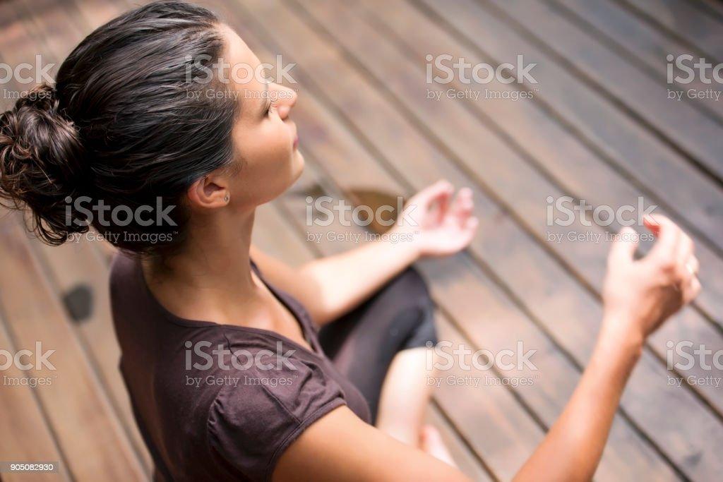 Elevated view of woman meditating - Foto stock royalty-free di Adulto