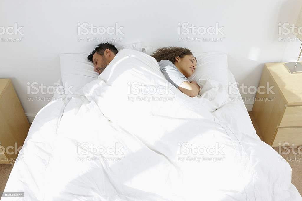Elevated view of young couple sleeping in bed royalty-free stock photo
