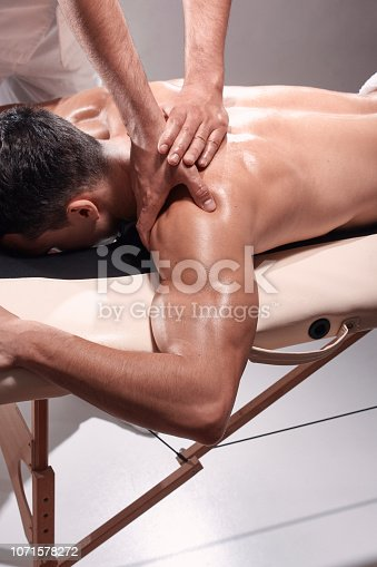 1071579572istockphoto elevated view, two young man, 20-29 years old, sports physiotherapy indoors in studio, photo shoot. Physiotherapist massaging patient shoulder with his hands. 1071578272