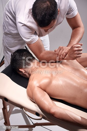 1071579572istockphoto elevated view, two young man, 20-29 years old, sports physiotherapy indoors in studio, photo shoot. Strong Physiotherapist hard massaging relaxed patient neck back side, with his elbow. 1071579346