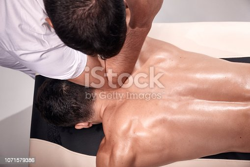 1071579572istockphoto elevated view, two young man, 20-29 years old, sports physiotherapy indoors in studio, photo shoot. Strong Physiotherapist hard massaging, relaxed but muscular patient neck back side, with his elbow. 1071579386