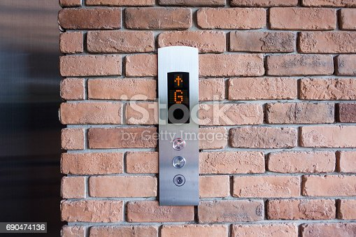 istock Elevator button showing G floor and up arrow sign. On old red brick wall 690474136
