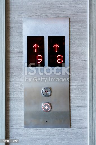 istock Elevator buttons panel against wooden background 859161258