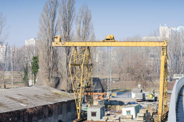 Elevator crane on abandoned junk yard for metal waste with city background. stock photo