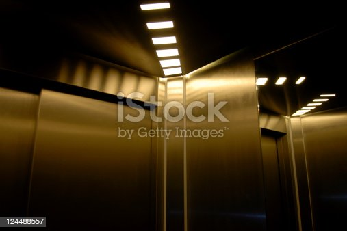Inside a shiny and high tech elevator with a mirror giving reflections.