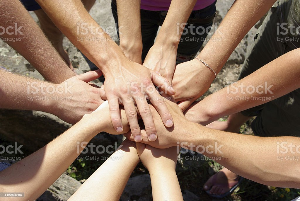 Eleven hands together in a circle as a sign of teamwork stock photo