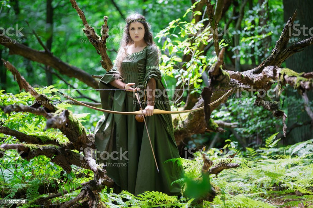 Beautiful female elf archer in the forest hunting with a