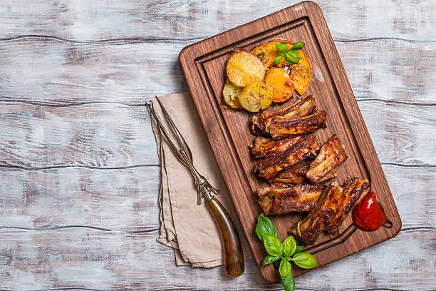 D'elicious Grilled Pork Rib D'elicious Grilled Pork Rib and Fried Potato Wedges with Sauce on wooden cutting board, top view human rib cage stock pictures, royalty-free photos & images