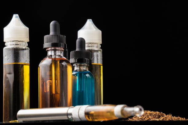 E-liquid bottles and e-cigarette with pile of grinded tobacco leaves stock photo
