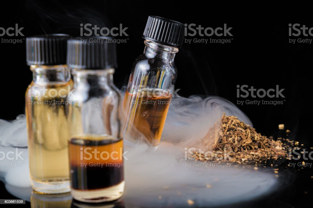 E-liquid bottles next to grinded tobacco leaves and smoke cloud stock photo