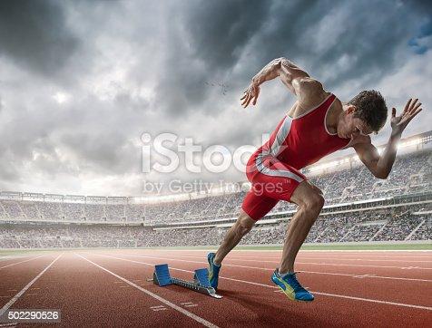 istock Elite 100m Runner Sprints From Blocks in Floodlit Stadium 502290526