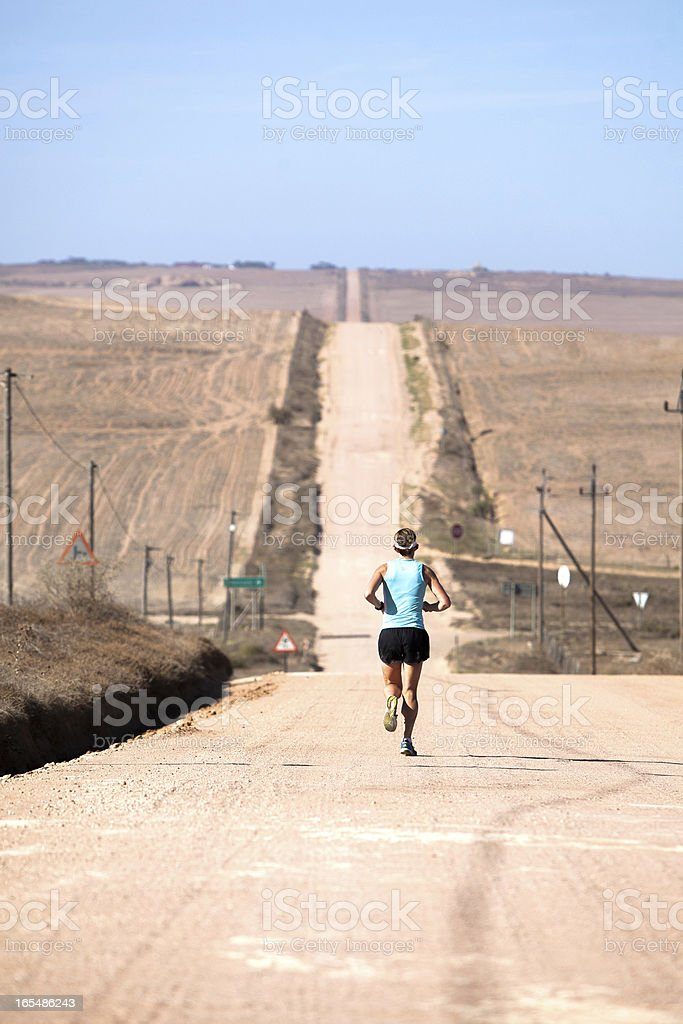 Elite female athlete running along a gravel road royalty-free stock photo