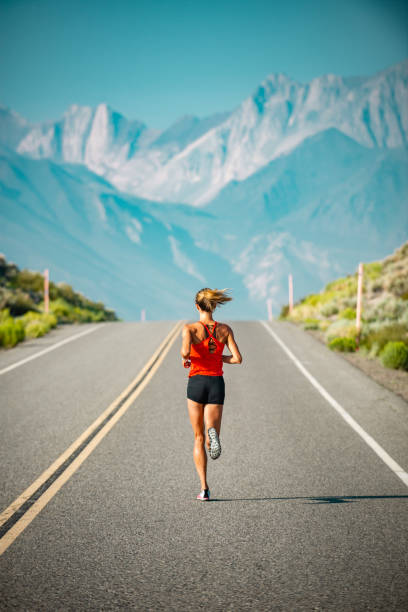 Elite Women Athlete Running Up A Road in the Sierra Mountains, California stock photo