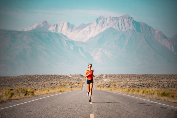 elite women athlete running up a road in the sierra mountains, california - endurance stock pictures, royalty-free photos & images