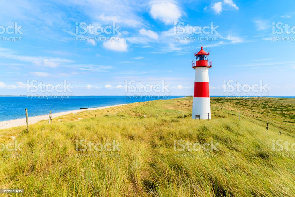 Ellenbogen lighthouse on sand dune against blue sky with white clouds on northern coast of Sylt island, Germany stock photo