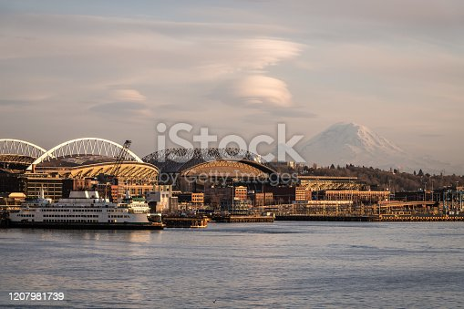 A ferry on Elliott bay with mount rainier in the background.