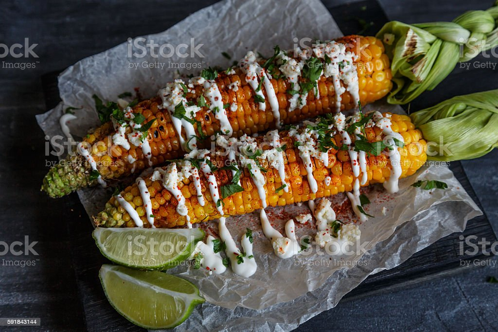 Elote or Mexican grilled corn on the cob served with stock photo