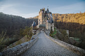 Beautiful view of famous Eltz Castle in scenic golden morning light at sunrise with blue sky on a sunny day in fall with retro vintage VSCO style filter effect, Wierschem, Rheinland-Pfalz, Germany