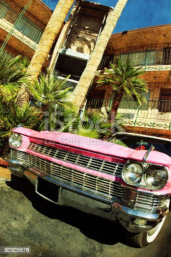 A bright pink Cadillac at a retro hotel.  Photo has an aged texture added to it for a dramatic effect.