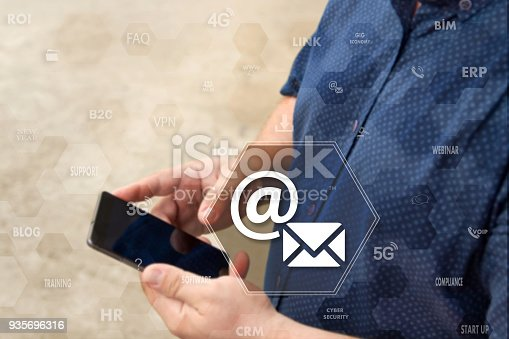 860524646istockphoto Email button on the touch screen with a blur background of the businessman with the phone.The concept of email , mail, email marketing 935696316