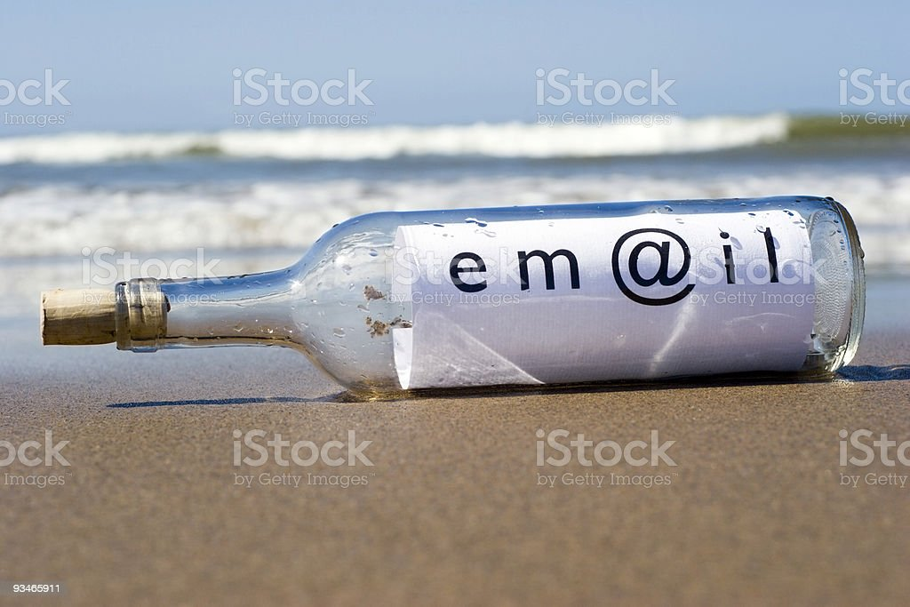 email communications - message in a bottle on beach stock photo