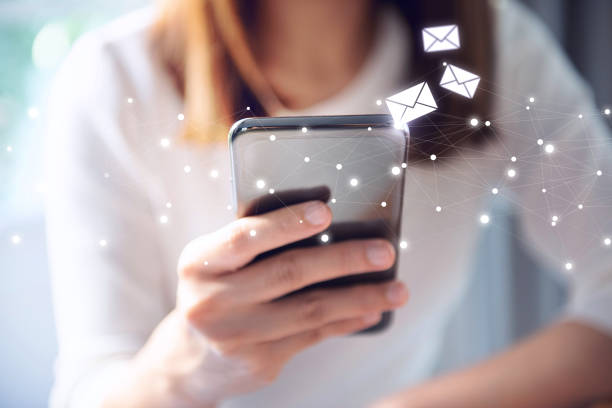 Email concept, Closeup Woman hand using mobile smartphone with email icon. stock photo