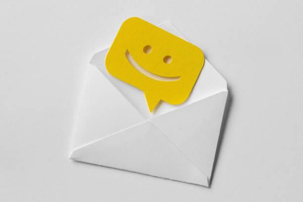 envelope de correio electrónico com sorrindo bolha mensagem sobre fundo branco - mensagem - fotografias e filmes do acervo
