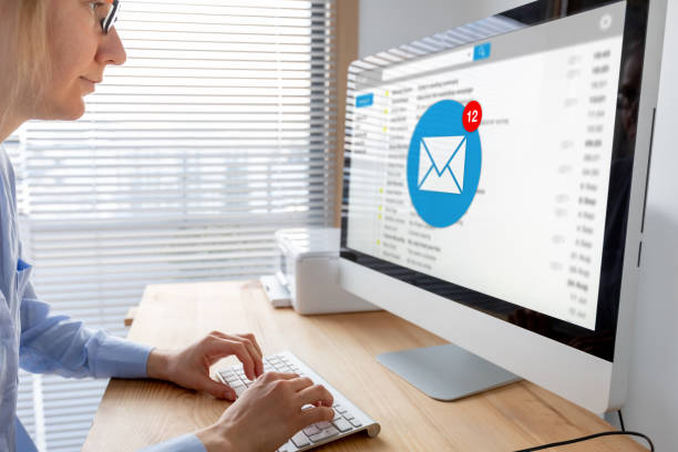 Email inbox notification with female business person receiving new incoming message at work, e-mail communication marketing  and interruption concept, employee working with computer in modern office stock photo