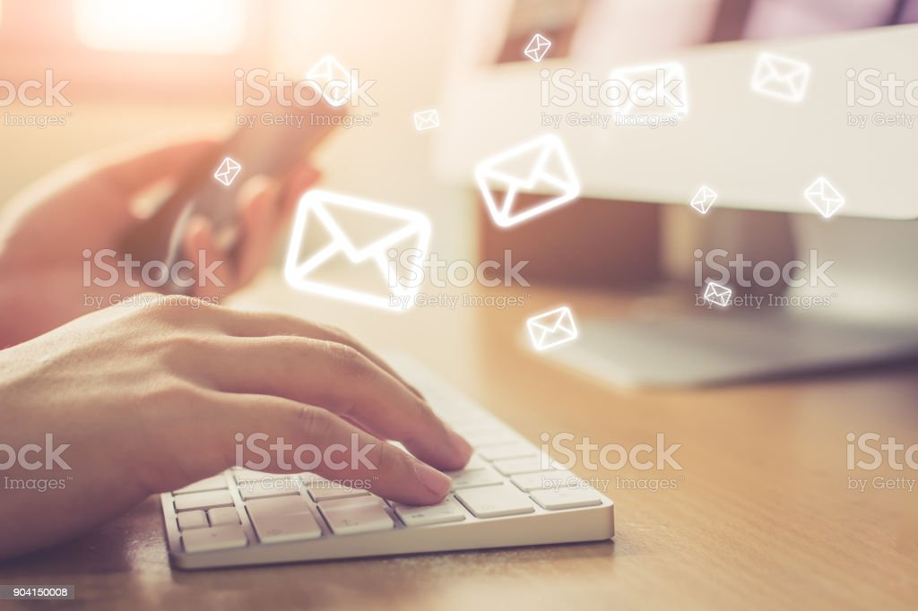 Email marketing and newsletter concept, Hand of man sending message and mobile phone with email icon stock photo