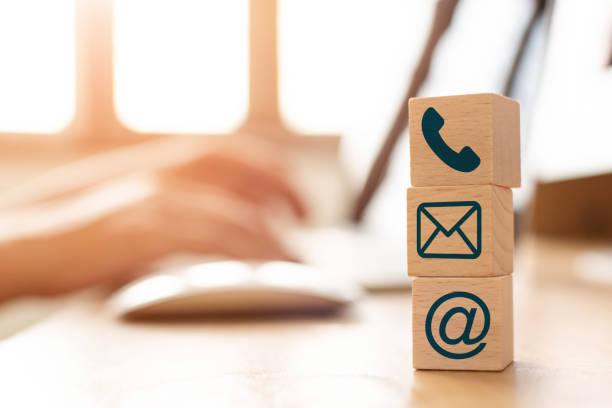 Concepto de marketing de correo electrónico, mano a mano utilizando el mensaje de envío de computadora con bloque cubo de madera con dirección de correo icono y símbolo de teléfono - foto de stock