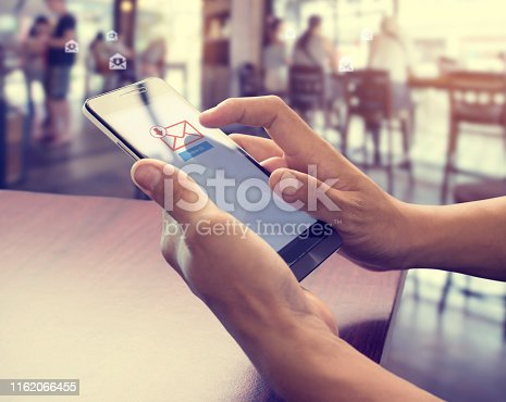 Hand of male using mobile phone to open new E-mail message inbox with email symbol and envelope icon. Email marketing and newsletter concept