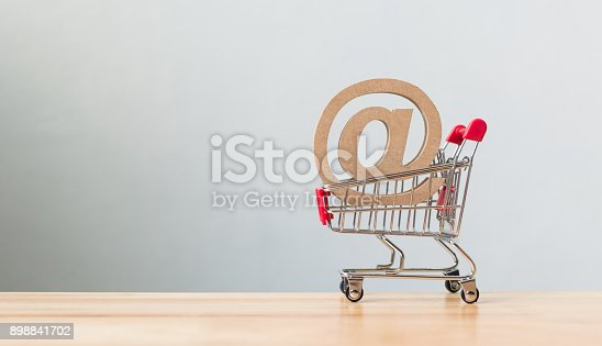 istock Email marketing concept, Wooden symbol email address into shopping cart on table 898841702