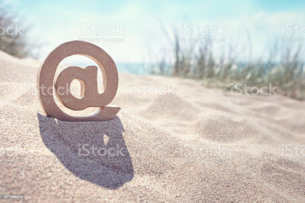 E-mail @ symbol at the beach stock photo