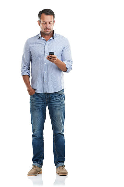 Emails on the go Full length shot of a handsome man checking his phone against a white backgroundhttp://195.154.178.81/DATA/istock_collage/a3/shoots/785221.jpg hands in pockets stock pictures, royalty-free photos & images