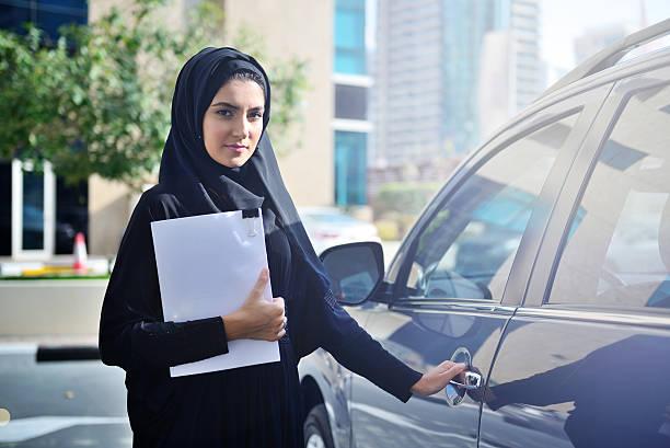 Emarati Arab Business woman getting inside the car stock photo