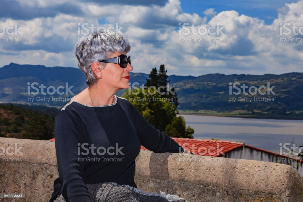 Embalse del Tominé in Guatavita, Colombia. A Senior Colombian Lady Sits by the Lakeside and Looks Towards the Placid Waters royalty-free stock photo