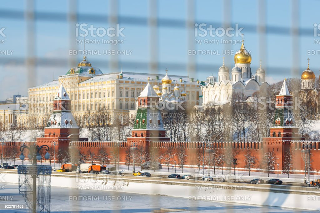 Embankment of the Moscow river, view of the Kremlin wall, towers and churches on the territory of the Moscow Kremlin in winter. The photo was shot through a construction net from the opposite side of the Moscow river stock photo